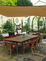 Walled courtyard with dining table shaded by suspended sail. Raised beds planted with figs, hydrangea, begonia, petunia. Reclaimed brick and stone. Metal pergola with wisteria.