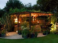Night view of pergola seating area, flanked by phormium. Vine on pergola supporting hanging lanterns and rope lights. Pots of agapanthus, bamboo, acer, fern, canna, palm, geranium.