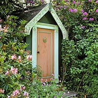 Tucked away in shade of rhododendron, a childrens playhouse.