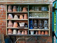 Shelves built from reclaimed timber offcuts house terracotta plant pots, glass jars and lanterns, making use of a wall for storage in this tiny town garden.