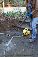Woman using a Karcher high pressure jet spray to clean a patio surface