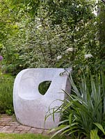 Sculptural moulded concrete chair, dogwood and roses behind and clump of Astelia chathamica to right side.