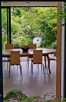 View from inner courtyard, through modern dining room extension, over terrace and down leafy garden of sumach, olive, astelia, magnolia, birch, dogwood, astilbe, fern.