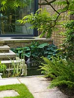 A bubbling, circular pool on the terrace feeds a rectangular pool below, edged in hosta, iris and fern and beneath a sumach.