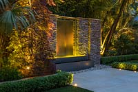 Town garden designed by Kate Gould, seen at night. Stainless steel water feature set into a dry stone wall, a red Japanese maple floodlit to one side.