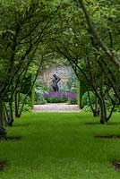 An avenue of Malus toringo var. sargentii trees leading to a contemporary sculpture in a walled garden.