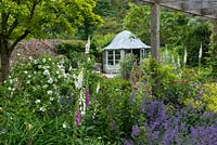 A mixed border planted with philadelphus, foxglove, catmint and alchemilla in front of a summer house with domed lead roof,