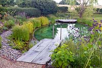 View of wooden decking leading to a swimming pond.