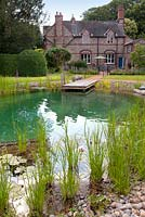 View of a house and natural swimming pond. July.