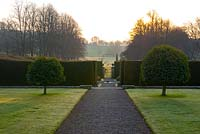Sunrise over formal garden with path leading to clipped Yew hedges, lawns with Prunus lusitanica - Ammerdown House, Somerset