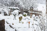 Winter scene in kitchen garden with edged patches, wooden bird feeder, bistro table and a cast iron garden fence