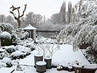 River Thames garden designed by Andy Sturgeon. Box topiary, grasses and architectural plants covered in snow.