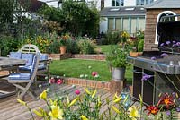 Riverside deck with barbecue, dining table and chairs, is edged in pots and bed of oriental lilies, daylilies, Verbena bonariensis and annual poppies. A step up leads to a lawn and raised bed.