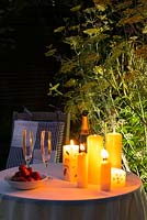 Romantic drinks by candlelight in the garden at night