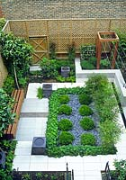 Private garden in Hackney, London. Tile paving, slate mulch, slate fountains, wooden fencing and trellis. Planting includes Buxus sempervirens balls, Alchemilla mollis, Nandina domestica, Pittosporum tobira, ferns, herbs, Magnolia grandiflora. Design: Joe Swift and The Plantroom