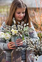 Girl with arrangements of Christmas roses and catkins.