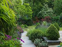 A natural flagstone path leads along a mixed border and topiary through to the lawn.