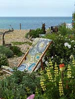 Deck chair draped with a rag rug, handcrafted by garden owner textile artist Liz Shackleton