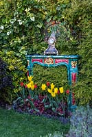 An old, painted fire surround mirror and clock set into evergreen hedge of ivy, lonicera and pittosporum, and planted with yellow Tulipa 'West Point' and red Tulipa 'Red Shine' and heuchera.