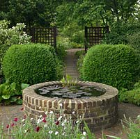 A small raised pond provides a focal point at the end of a shady path.
