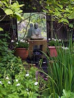 Hidden in shady corner beneath magnolia tree, a tiny water feature with statue of Buddha perched above miniature waterfall, a mirror behind. Edged in white iris, geranium.