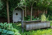 A shady corner of a walled garden with covered wooden seat, a small pond made from a galvanised metal animal feeding trough and shade tolerant planting including hosta and box.