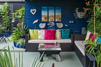 A covered seating area with seaside inspired decorations, sofa and table.