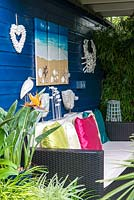 A covered seating area with seaside inspired decorations and sofa.
