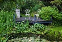 A small raised deck and seating area overlooking a pond.