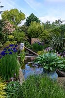 View along the pool, over lavender, potted hosta, Iris sibirica Caesar's Brother, Hakonechloa macra and pink Persicaria bistorta Superba and male ferns. Left border - photinia. Right border - phormium, Chusan Palm and maple. Pond sculpture by Peter Hayes.
