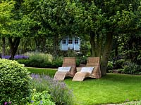 Wicker loungers in shade beneath a holly tree with the children's summer house beyond.