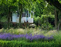 An elevated children's playhouse in a shady area with Hydrangea and Acanthus mollis. Box, lavender, Stipa tennuissima and Allium seedheads make up the foreground planting.