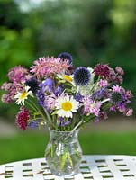An arrangement of flowers picked from the garden including Anthemis, Echinops, lavender, campanula, Sanguisorba and Astrantia.
