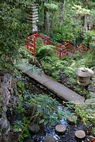 Stone bridge crossing pond with round stepping stones at Monte Palace Tropical Garden, Madeira, in the Oriental garden, with Japanese artefacts and bright red railings
