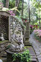 Japanese artefacts in the Oriental garden at Monte Palace Tropical Garden, Madeira, with red arch in the distance