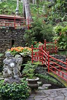 Clivia miniata with Buddha statue in Oriental garden at Monte Palace Tropical Garden, Madeira, with red railings
