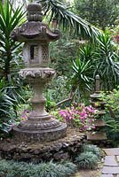 Japanese lantern and pagoda sculpture in Oriental garden at Monte Palace Tropical Garden, Madeira with carex, azaleas and ferns