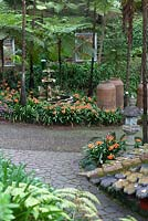 Large urns and Japanese lantern in Monte Palace Tropical Garden, Madeira, with fountain fringed by clivia miniata