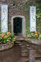 Tiled panels and doorway into the bank at Monte Palace Tropical Garden, Madeira, with clivia miniata fringing the pond