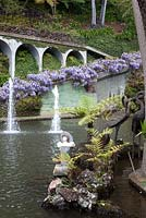 Wisteria clad wall leading down to the Central Lake at Monte Palace Tropical Garden, Madeira, with water jets, and statuary
