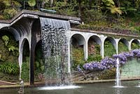 Waterfall into the Central Lake at Monte Palace Tropical Garden, Madeira, with wisteria clad wall, and cherub water feature