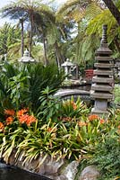 Oriental garden with series of ponds at Monte Palace Tropical Garden, Madeira, with pagodas, lanterns, bridges and clivia miniata