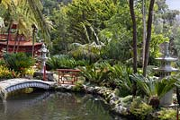 Oriental garden at Monte Palace Tropical Garden, Madeira with series of ponds, with bridges, pagodas and lanterns, and planted with cycads and clivia miniata