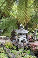 Oriental garden at Monte Palace Tropical Garden, Madeira, with Japanese lanterns, pagodas, seats and railings and planted with tree ferns, moss and ferns