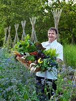 Raymond Blanc stands in his organic vegetable garden against a backdrop of borage and can wigwams for beans, in his arms a box of fresh produce.
