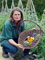 Jo Campbell with a basket of freshly picked edible flowers to include borage, marigold, courgette, thyme, lavender, borage, bean and viola.