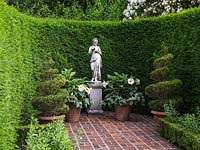 Classical statue on plinth in formal brick courtyard enclosed in curving yew hedge. Pots of box spirals and Datura.
