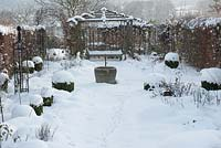 Snow garden with box balls, gazebo and bench backed by tall hedge. Animal footprints left in the snow.