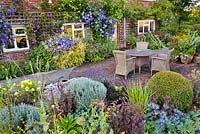 Planting includes: bed by house - Lonicera 'Baggesen's Gold', Clematis 'Perle d'Azur', Venosa Violacea, Geraniums 'Rozanne' and 'Ann Folkard'. In raised bed: Buxus, Santolina chamaecyparissus, Sedum 'Matrona', Eryngium 'Big Blue', Panicum 'Rotstrahlbusch', Ophiopogon plansicapus 'Nigrescens', Oenothera missouriensis, Morinia longifolia'