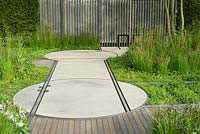 Rails embedded in pathway and rotating discs to carry moveable 'shack'. The Cloudy Bay and Bord na Mona garden, Chelsea Flower Show 2015